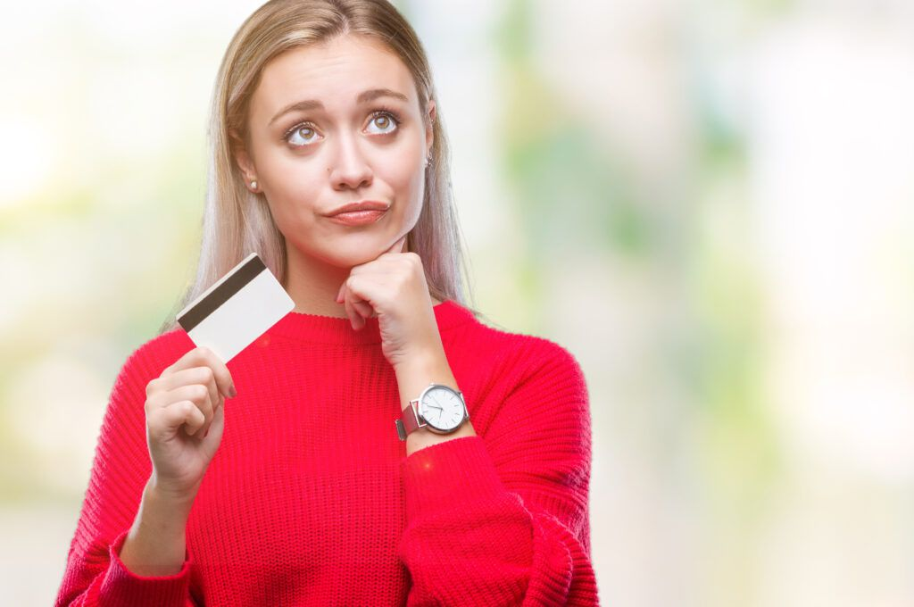 Young blonde woman holding credit card over isolated background serious face thinking about question, best payment processors concept