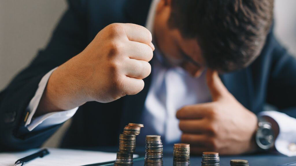 Businessman banging fist on desk behind declining piles of coins, insolvency concept