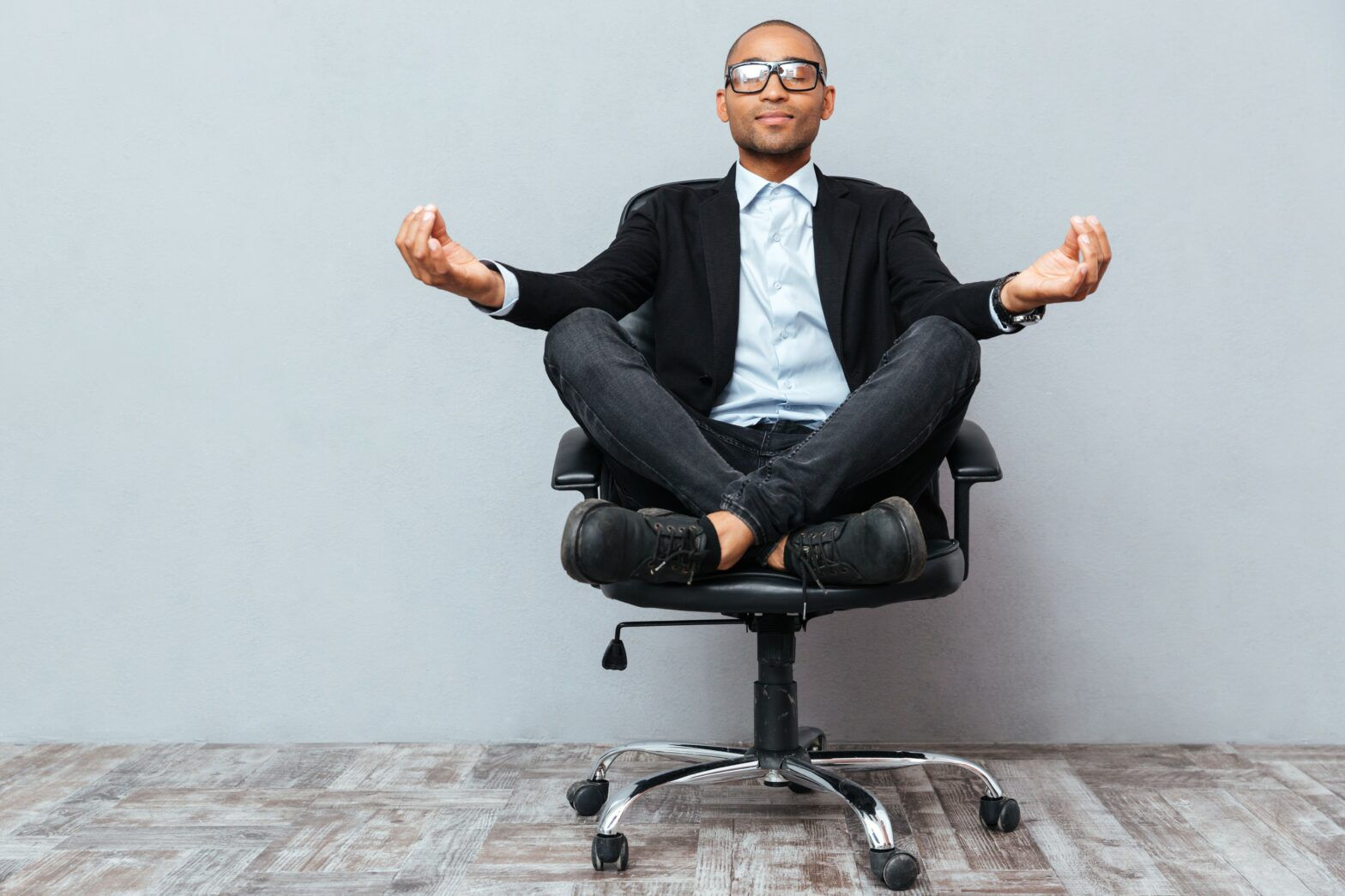 Man sitting cross-legged in office chair in yoga pose, office chair concept