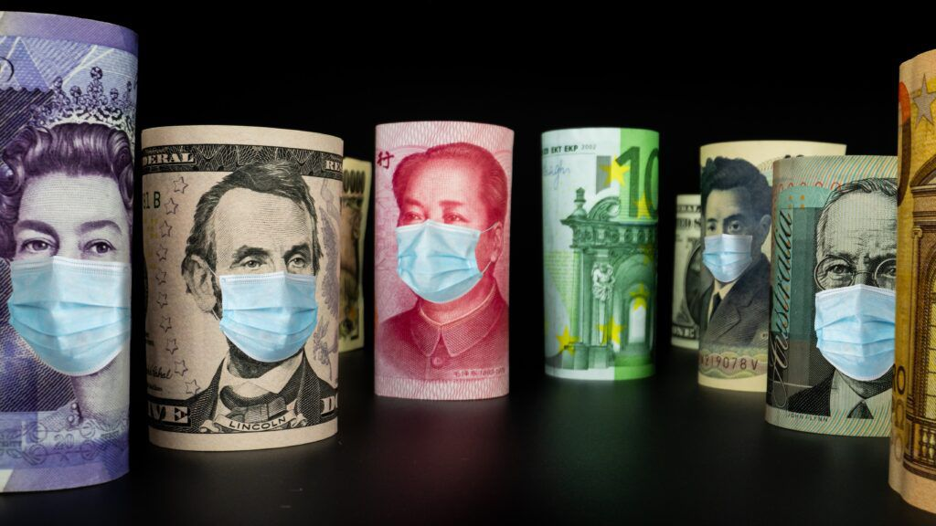 Rolled international currency banknotes wearing facemasks, recovery loan scheme concept