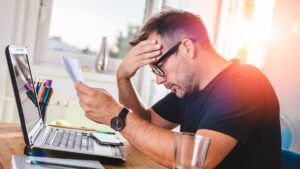 Man holding head in hands as he reads letter over laptop, businesses debt concept