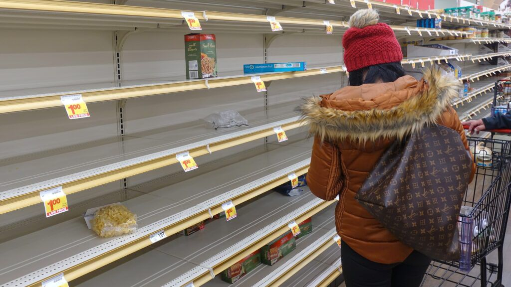 Woman with back to camera surveying empty supermarket shelves, supply chain crisis concept